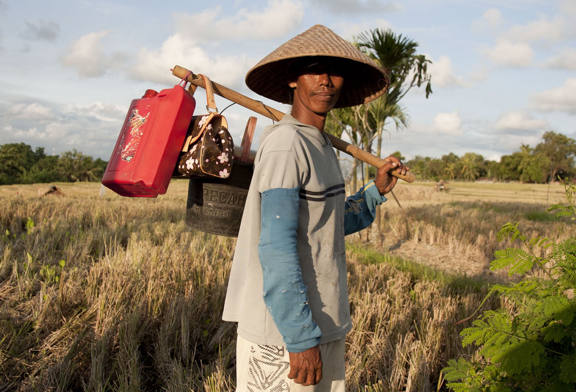 Farmer in Bali carrying Louis Vuitton bag